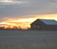 Sun setting over a barn in a field